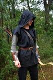 Mittelalterlicher Bogenschütze mit schwarzer Haube und farbigen Pfeilen im Beben steht mit Bogen stockfoto
