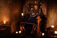 Mittelalterlicher König auf Thron im alten Schlossinnenraum stockfotos