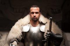 Mittelalterlicher Krieger im Rüstungs- und Pelzumhang Lizenzfreie Stockfotografie