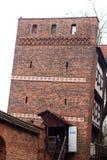 Mittelalterlicher lehnender Verteidigungsturm von Torun über weißem Himmel Stockfotografie