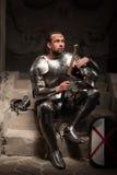Mittelalterlicher Ritter, der auf den Schritten von altem sitzt lizenzfreie stockfotos
