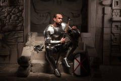 Mittelalterlicher Ritter, der auf den Schritten von altem sitzt Lizenzfreie Stockbilder