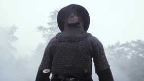 Mittelalterlicher Soldat in chainmail Rüstung und mit einem Sturzhelm auf seinem Kopf im Regen stock video