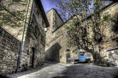 Mittelalterliches italienisches Dorf mit blauer Rollerbiene Stockfotografie