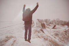 Mittelaltermann, der in schöne Winterlandschaft springt Mannbetrachtung auf verlassenen Freistilmotocrossrampen Addieren Sie colo Stockbild