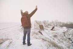 Mittelaltermann, der in der schönen Winterlandschaft steht Mannbetrachtung auf verlassenen Freistilmotocrossrampen Addieren Sie F Lizenzfreies Stockfoto