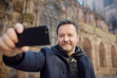 Mittelaltermann, der selfie bewegliches Foto mit berühmter Kathedrale Notre Dame von Straßburg auf Hintergrund macht stockfoto