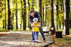 Mittelaltervater, der seinem Kleinkindsohn zeigt, wie man einen Roller in einem Herbstpark reitet Stockfoto