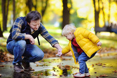 Mittelaltervater, der zusammen mit seinem Kleinkindsohn in einem Herbstpark spielt Lizenzfreie Stockfotografie