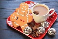 MittelDraufsicht der lebkuchenmänner mit Kaffee auf rotem Teller lizenzfreies stockfoto