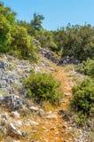 Mittelmeer- felsige Landschaft mit einem Fußweg des roten Erde-throu Stockbild