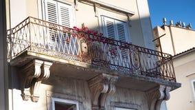 Mittelmeer- und Weinlese-Balkon mit roten Blumen in der Hafenstadt Rijeka in Kroatien lizenzfreies stockfoto