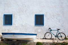 Mittelmeerbootsfahrrad und weiße Wand im Weiß Stockfotografie