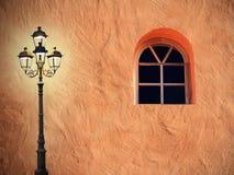 Mittelmeerhausfassade mit traurig blickender Laterne und gewölbtem Wind Lizenzfreies Stockfoto