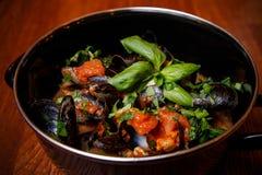 Mittelmeermiesmuscheln in der Tomatensauce mit frischen Kräutern lizenzfreies stockfoto