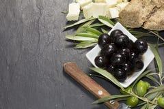 Mittelmeeroliven mit Feta, reinem Extraöl und frischem Brot über dunklem Stein Lizenzfreies Stockbild