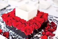 Mittelstück mit roten Blumen und Kerze Lizenzfreies Stockbild