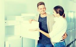 Mittelstandfamilienpaare, die neuen Kühlschrank wählen lizenzfreies stockfoto