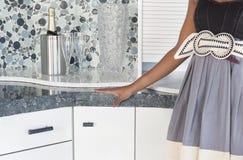 Mittelteil der Frau mit Champagner stellte auf Küchenarbeitsplatte ein Lizenzfreie Stockfotografie