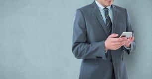 Mittelteil des Geschäftsmannes unter Verwendung des Handys über blauem Hintergrund Stockfotos