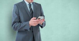 Mittelteil des Geschäftsmannes unter Verwendung des Handys Lizenzfreie Stockfotografie