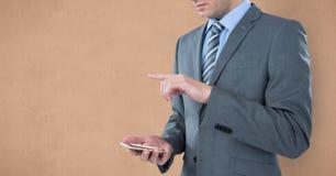 Mittelteil des Geschäftsmannes unter Verwendung des intelligenten Telefons gegen braunen Hintergrund Stockfotos