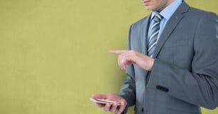 Mittelteil des Geschäftsmannes unter Verwendung des intelligenten Telefons gegen gelben Hintergrund Stockbild