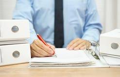Mittelteil des Geschäftsmannes arbeitend mit Finanzdokumenten an d Lizenzfreie Stockfotos