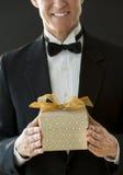 Mittelteil des glücklichen Mannes im Smoking, das Geschenkbox hält Stockfotos