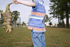 Mittelteil des Jungen mit Toy Dinosaur Stockbild