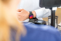 Mittelteil des Kunden zahlend durch Smartwatch lizenzfreie stockfotografie