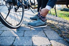 Mittelteil des Pendlers mit dem Fahrrad, das von der Arbeit in der Stadt, shoealaces binden reist lizenzfreies stockfoto