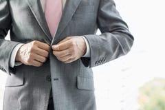 Mittelteil des reifen Geschäftsmannes seinen Blazer knöpfend lizenzfreie stockfotos