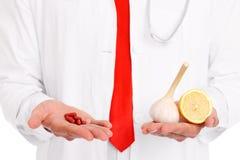 Mittelteil eines Doktors, der Pillen und Knoblauch mit Zitrone hält lizenzfreie stockfotografie