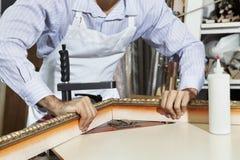 Mittelteil eines jungen Handwerkers, der an der Ecke des Bilderrahmens arbeitet Stockfotos
