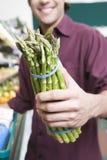 Mittelteil-Mann mit Spargel im Supermarkt Stockbilder
