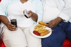 Mittelteil von überladenen Paaren mit der ungesunden Fertigkost, die Fernbedienung hält Stockbilder