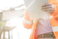 Mittelteilaufsichtskraft, die Klemmbrett an der Baustelle am sonnigen Tag hält Lizenzfreie Stockfotografie