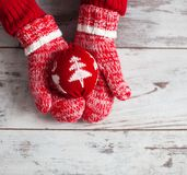 Mitten on wood floor. Mitten with christmas ball on wood floor. Winter decoration stock image