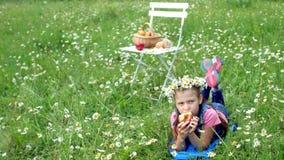 Mitten in einem Kamillenrasen im Gras liegt ein hübsches Mädchen von sieben Jahren, in einem Kranz von Gänseblümchen und fröhlich stock video