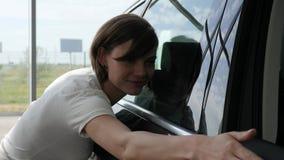 Mitten för den auto försäljningen, den unga kvinnliga kunden står den nästa automatiskn som är lycklig arkivfilmer