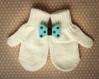 Mittens and bow. White mittens and turquoise bow Royalty Free Stock Image