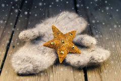 Mittens with Cristmas decoration on wooden background Royalty Free Stock Photos