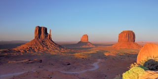 Mittens and Merrick Butte Monument Valley. Panoramic view of three desert buttes from elevated viewpoint at sunset. Winding dirt road and rocks in foreground stock photos