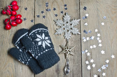 Mittens, stars and snowflake on a wooden table Royalty Free Stock Photos