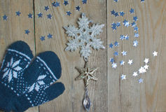 Mittens, stars and snowflake on a wooden table Stock Image