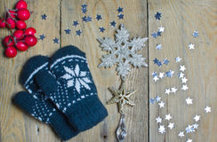 Mittens, stars and snowflake on a wooden table Royalty Free Stock Image