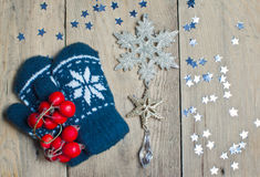 Mittens, stars and snowflake on a wooden table Royalty Free Stock Photo