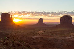 The Mittens at sunrise. East and West MItten Buttes and Merrick Butte in Monument Valley. The sun is rising. There are only a few clouds in the sky Royalty Free Stock Images