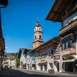 MITTENWALD, ГЕРМАНИЯ - взгляд известных покрашенных зданий и башни церков в историческом центре Mittenwald в Баварии стоковое изображение rf
